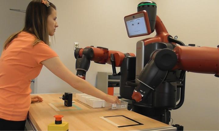 Eine Teilnehmerin trainiert den Montageprozess mit Baxter