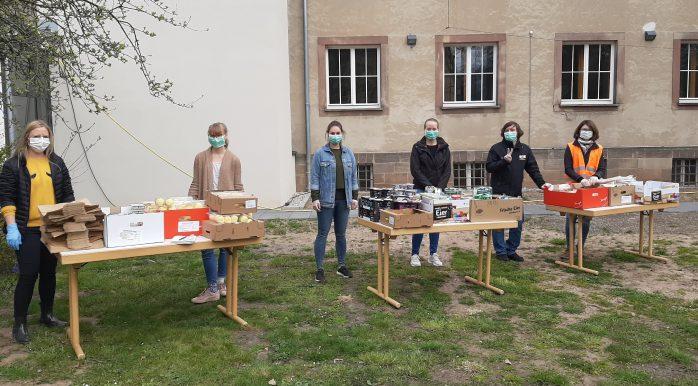 Junge Menschen stehen an Tischen voller Lebensmittel auf einer Wiese. Sie alle tragen Handschuhe und Mundschutz.